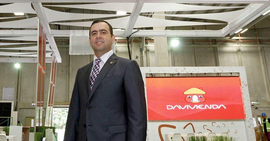 Una señor en traje y corbata posa junto al logo de Davivienda