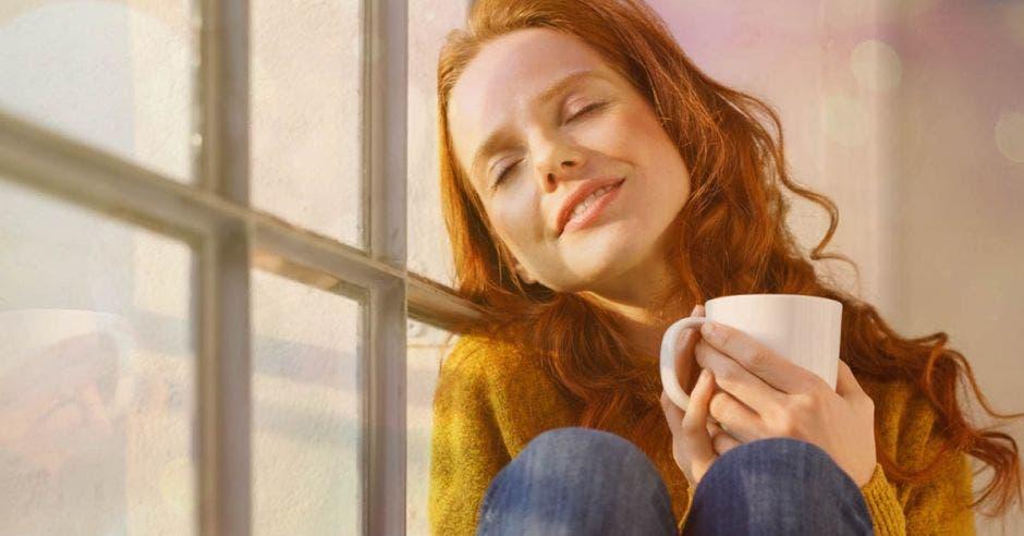 Una muchacha descansa junto a su ventana