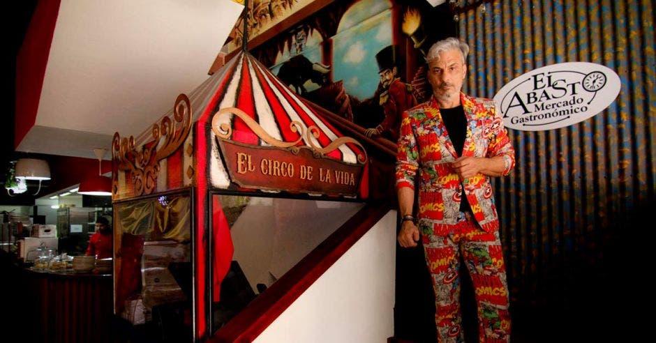 Un hombre de mediana edad posa junto a un quiosco en forma de carpa de circo