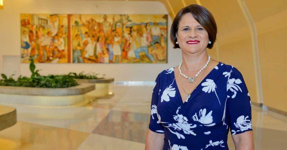 Una mujer viste un vestido azul en el lobby de un hotel