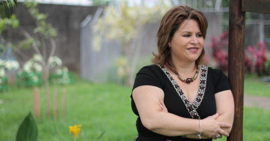 Silvia Bolaños posa en las afueras, en un jardín. Tiene el pelo corto y viste un enterizo color negro.