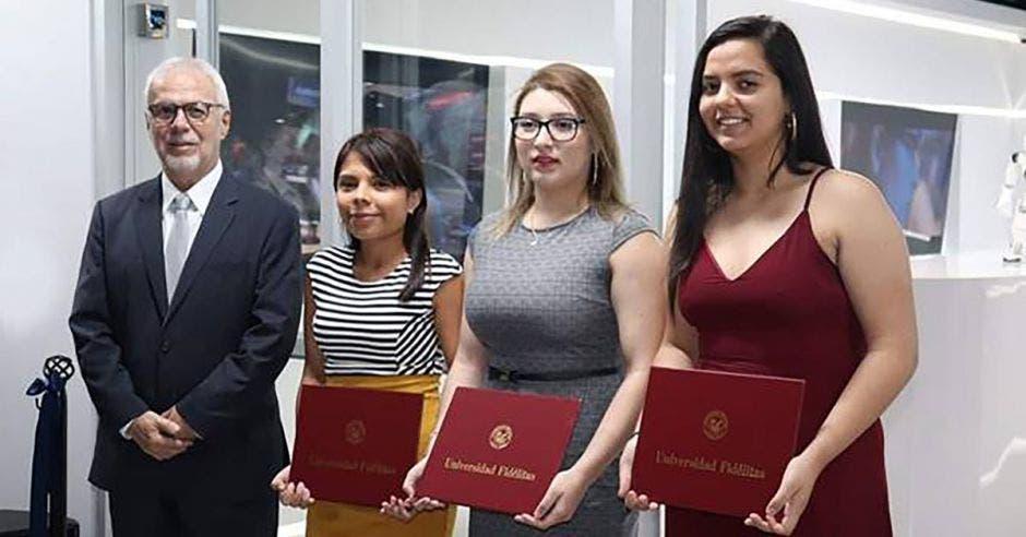 Roberto Rodríguez, rector de U Fidélitas en una graduación junto a tres estudiantes