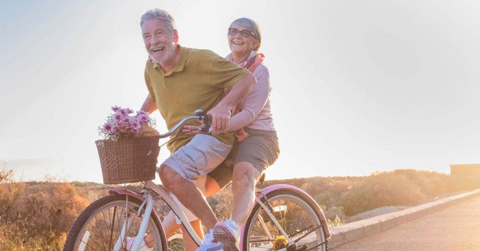 Dos adultos mayores sonrientes andan en bicicleta