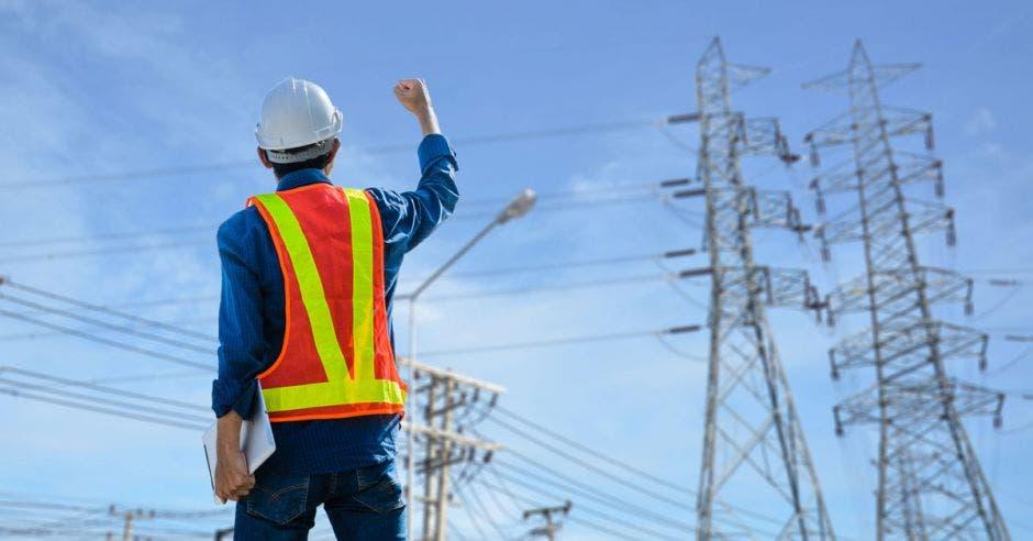 Trabajador eléctrico con tendido eléctrico defondo