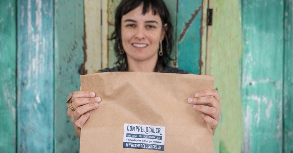 Una mujer de tez blanca sostiene una bolsa de papel