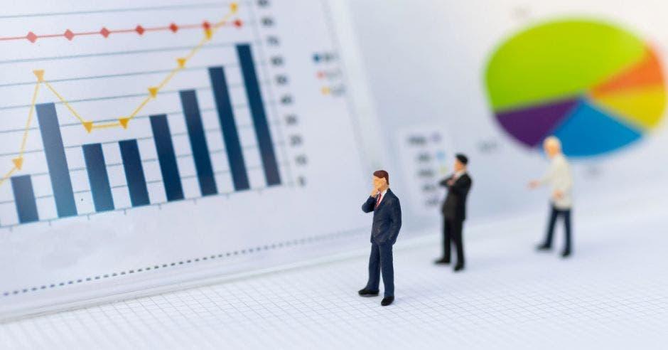 Un grupo de hombres ve una tabla con cifras estadísticas
