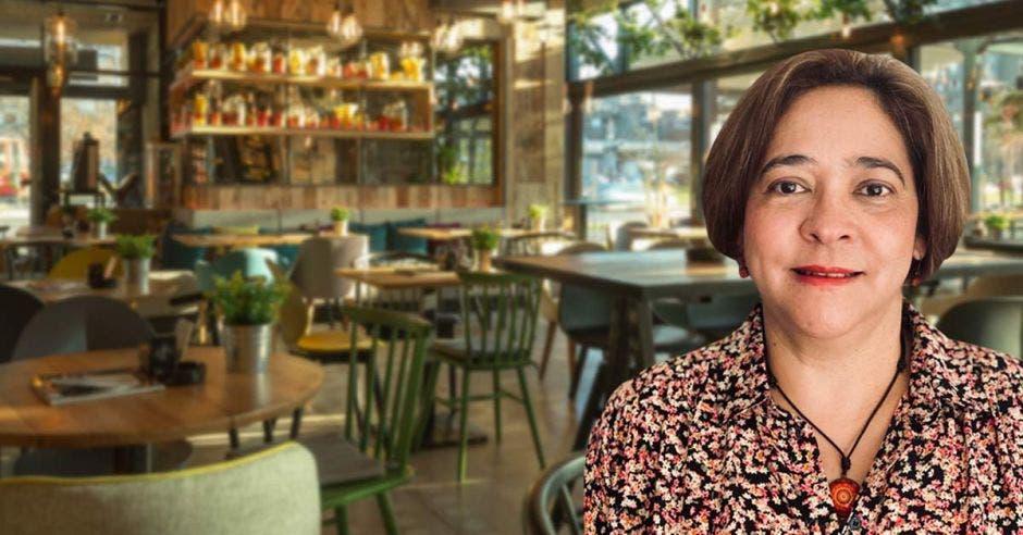 Una mujer de avanzada edad y pelo corto posa en un restaurante