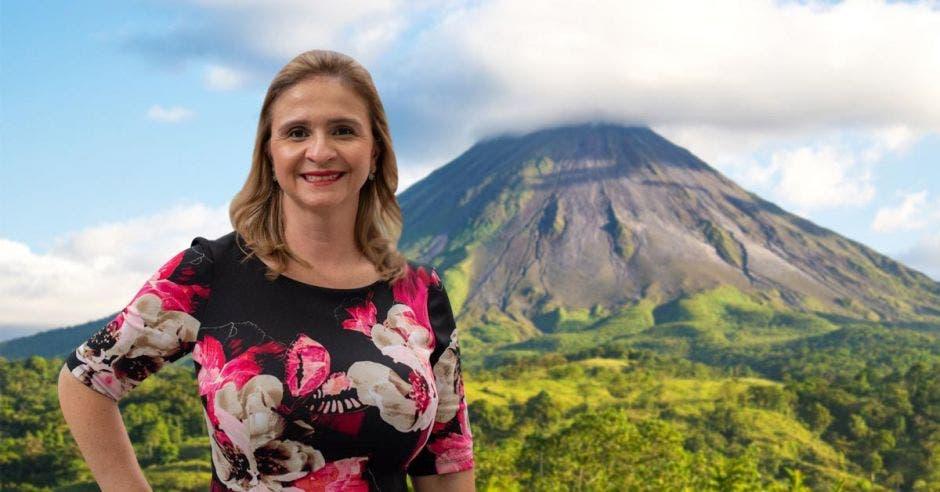 Una mujer posa sobre la figura del volcán Arenal