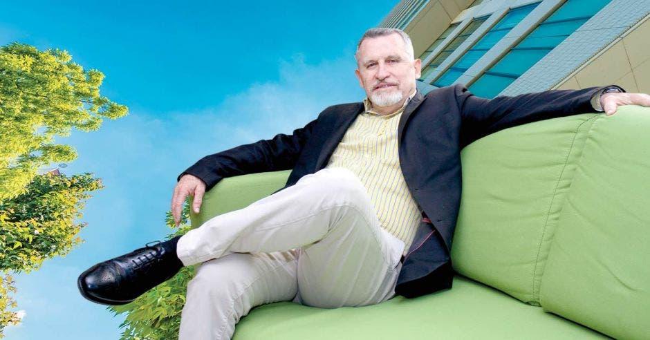 Un señor sentado en un sillón color verde
