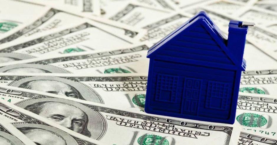 billetes de dólar con una casa de juguete encima