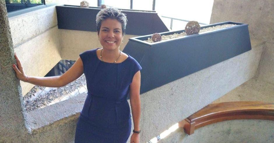 Una mujer con vestido azul posa en una escalera