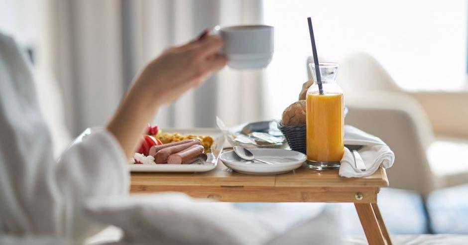 Una mujer toma jugo de naranja en su cama