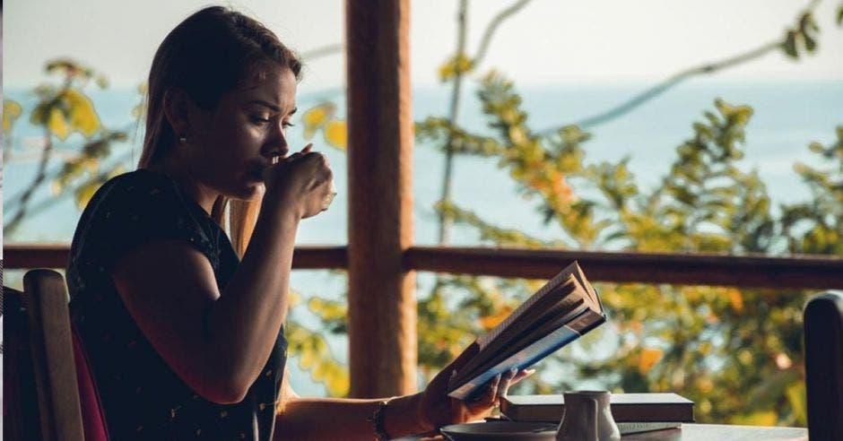 Una mujer joven toma café mientras lee un libro