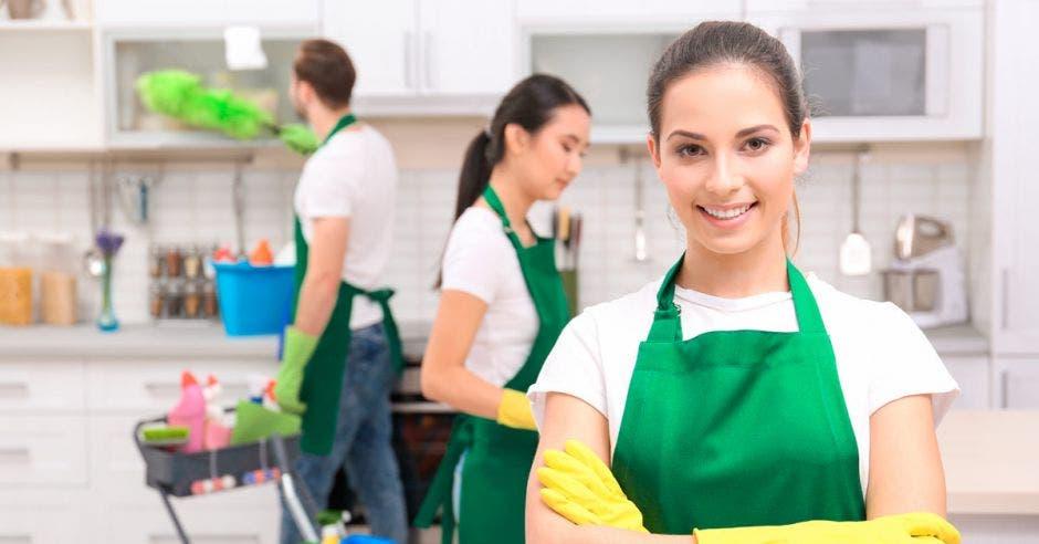 Un grupo de personas con delantales verdes limpia un local