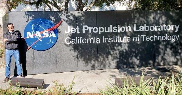 Un hombre adulto posa junto a un letrero que dice NASA
