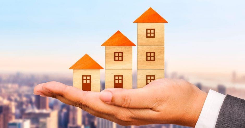 Una mano sostiene tres bloques de casas sobre una ciudad