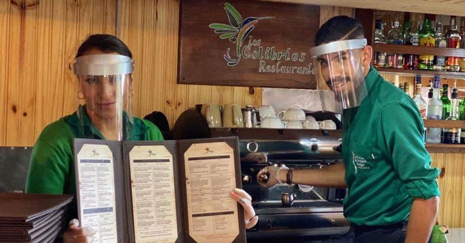 Dos empleados de un hotel visten sus uniformes verdes