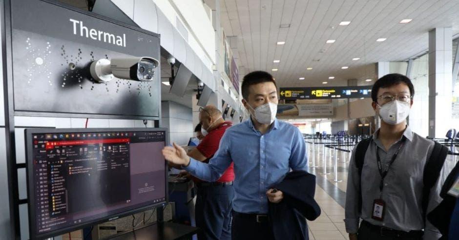 Un hombre asiático con mascarilla manipula una cámara térmica