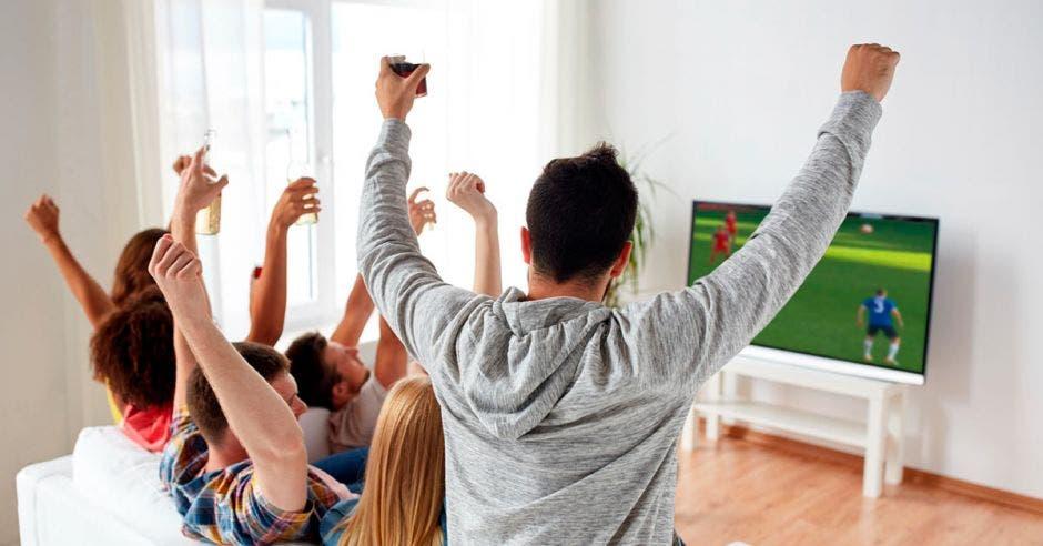 Personas viendo fútbol por TV