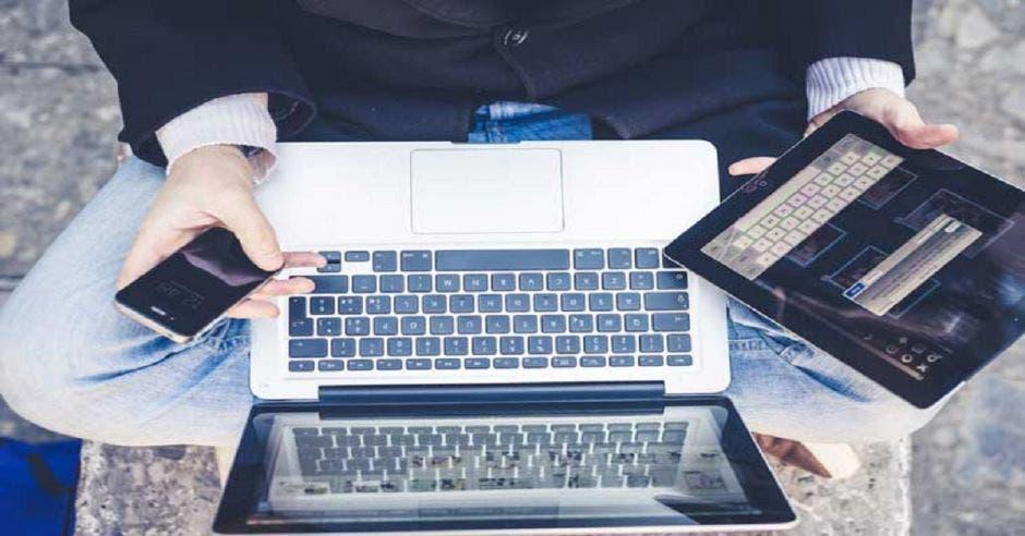Una persona con varios aparatos electrónicos