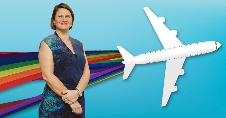 Una mujer con vestido azul posa frente a un avión blanco decorado con la bandera LGBT