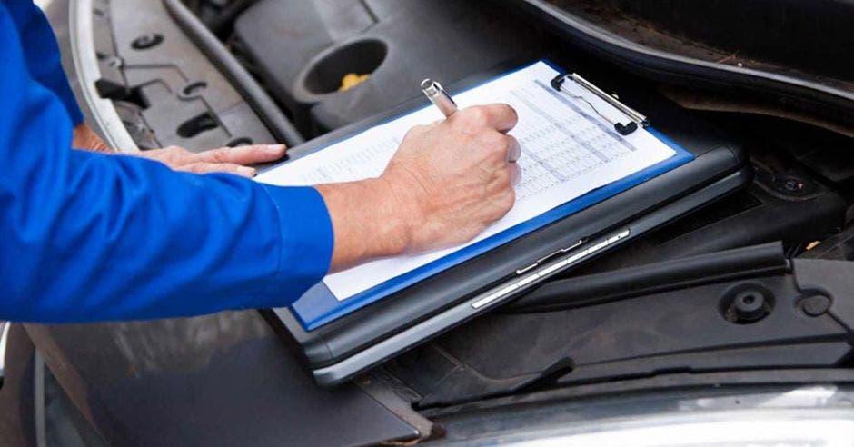 Mecánico revisando auto en revisión técnica