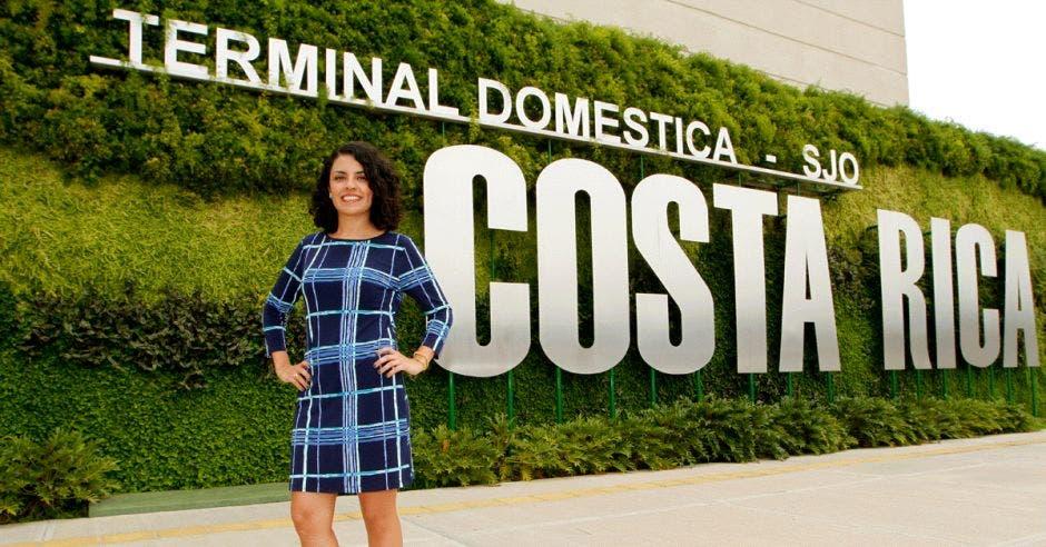 una mujer de pelo rizado y vestido azul posa frente a las letras de un letrero grande