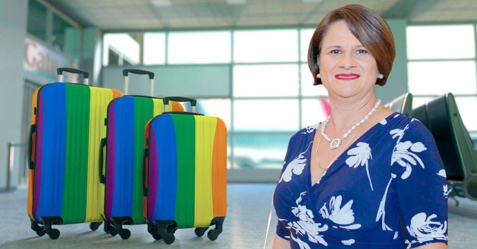 Una mujer de vestido azul posa junto a unas valijas de colores