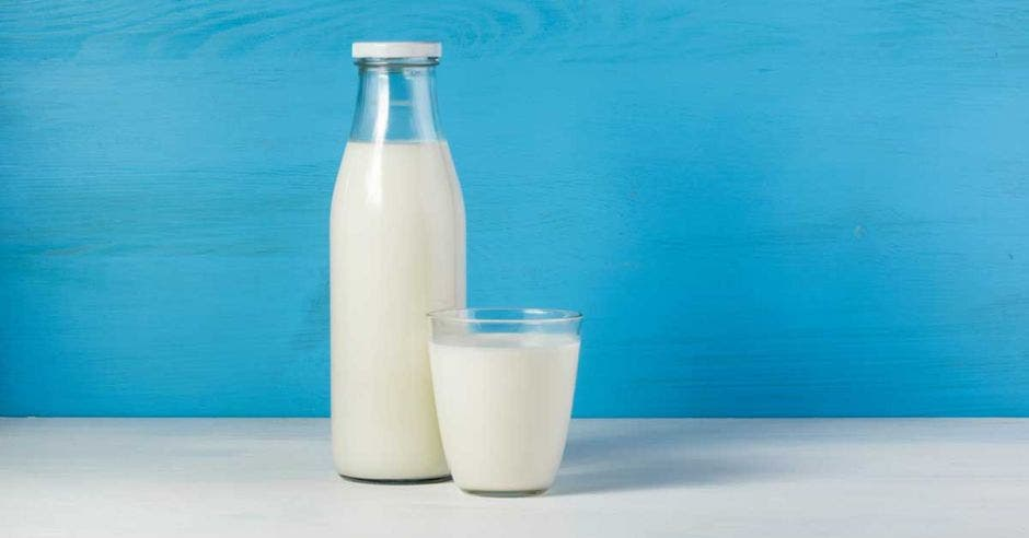 Una botella de vidrio con leche y un vaso de vidrio con leche