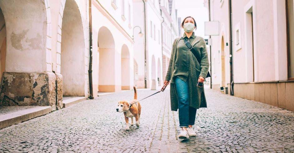 Una mujer pasea a su perro con una mascarilla puesta