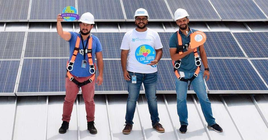 Tres colaboradores de SYKES en el área de paneles solares de uno de sus edificios