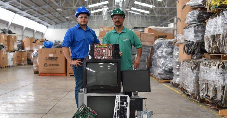 Dos trabajadores junto a una pila de desechos electrónicos