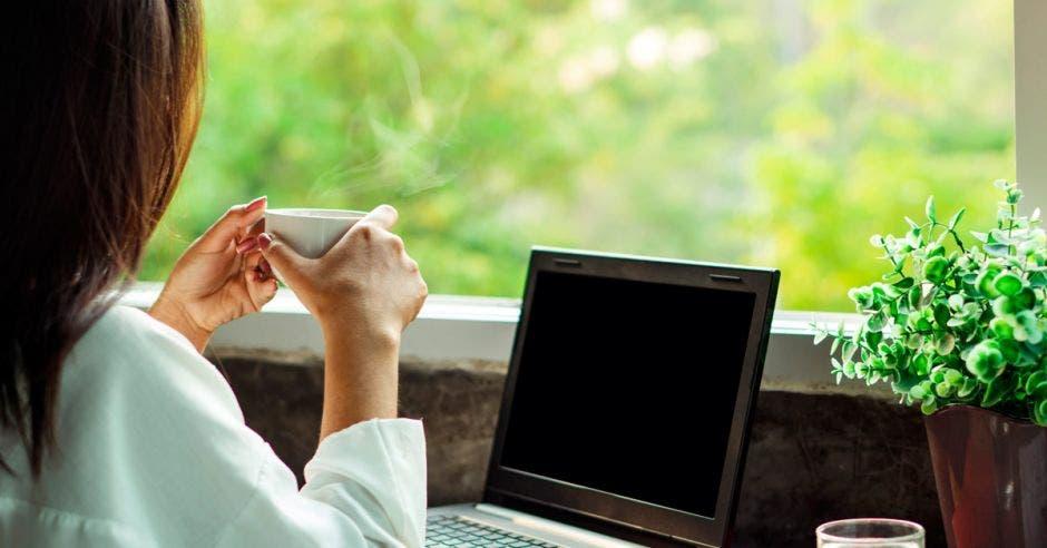 Una mujer en teletrabajo mira hacia el jardín mientras disfruta de un café.