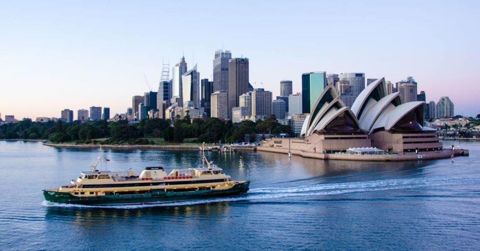 Un ferry de pasajeros pasa frente a la Ópera de Sydney temprano en la mañana, con el horizonte de la ciudad al fondo