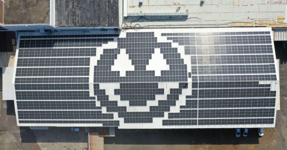 Logo de Dos Pinos sobre un techo cubierto con paneles solares