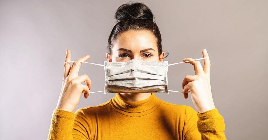 Una mujer utiliza una máscara desechable color blanco