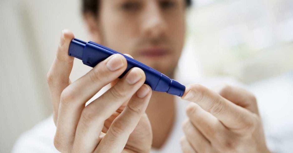 Alguien utiliza un glucómetro para medir su nivel de azúcar en la sangre
