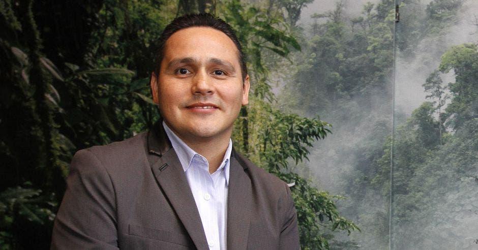 un hombre sonríe frente a un fondo de bosque nuboso
