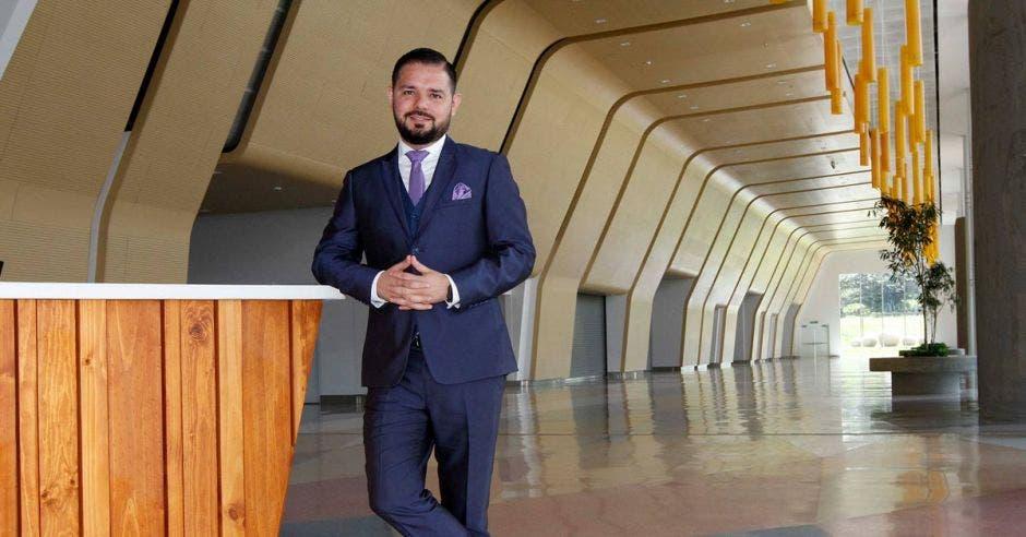 Un hombre con saco y corbata se apoya sobre un mostrador en el lobby de un centro de convenciones