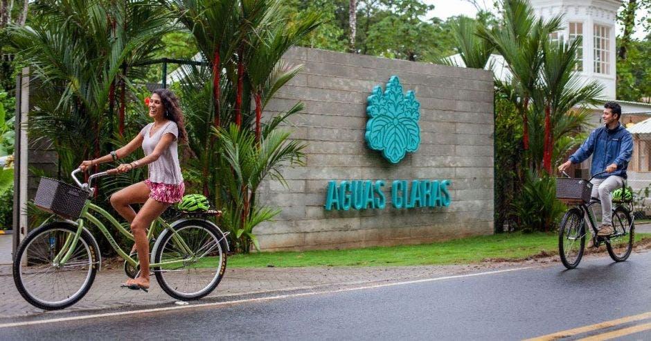 Dos personas en bicicleta pasan frente a un hotel