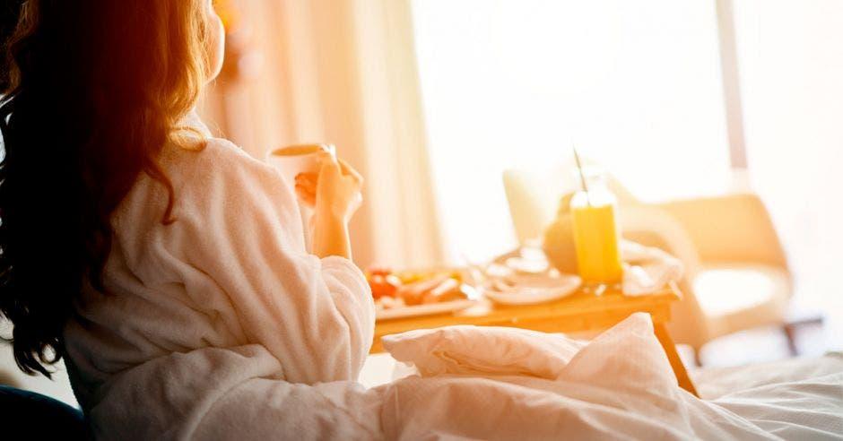 Una mujer disfruta de un desayuno en la habitación del hotel