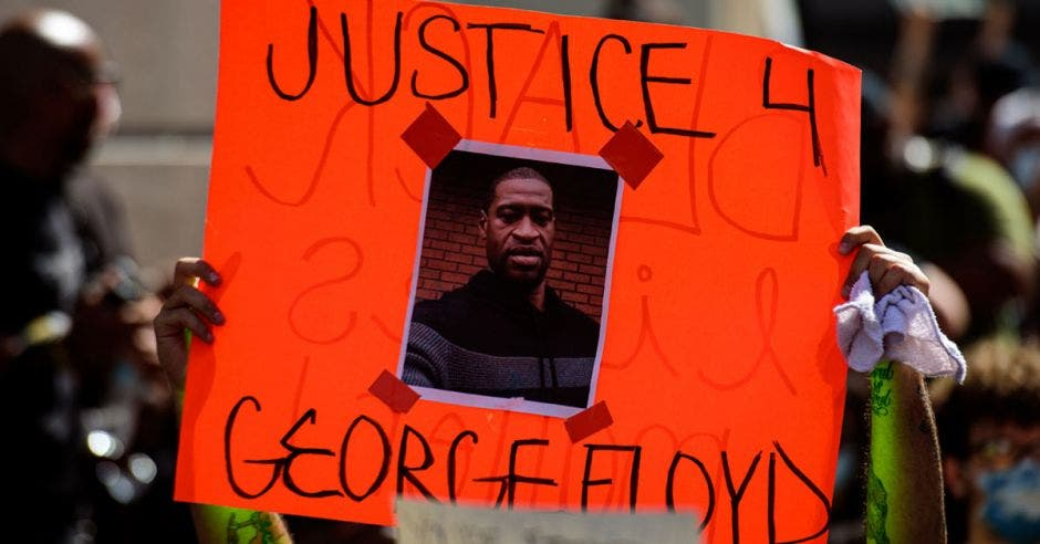 Una persona sostiene un cartel con la imagen de una persona negra
