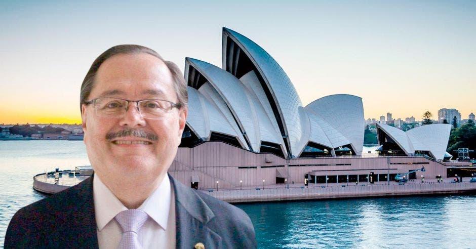 un hombre posa frente a una imagen de la Opera de Sidney