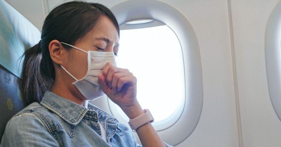 Mujer que se siente mal y que lleva mascarilla en el avión