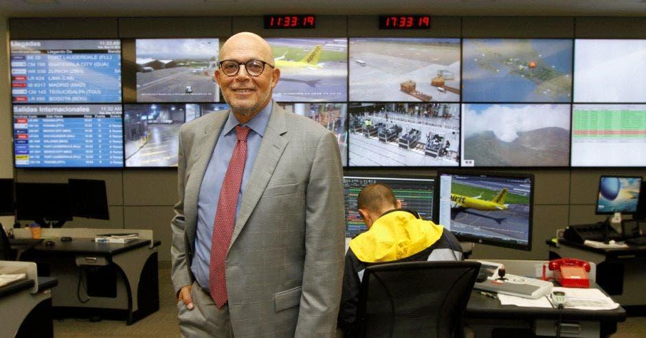 Un señor en traje gris posa frente a un puesto de control