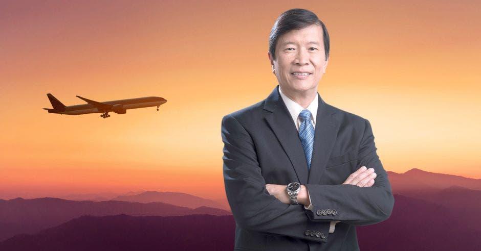 Un hombre con saco gris y corbata celeste posa sobre el fondo de un avión