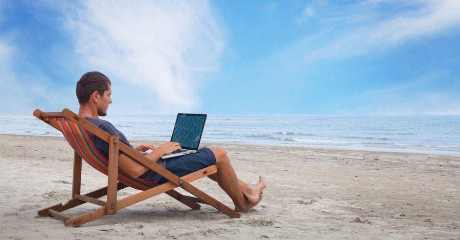 Un hombre en una tumbona revisa su computadora en la playa