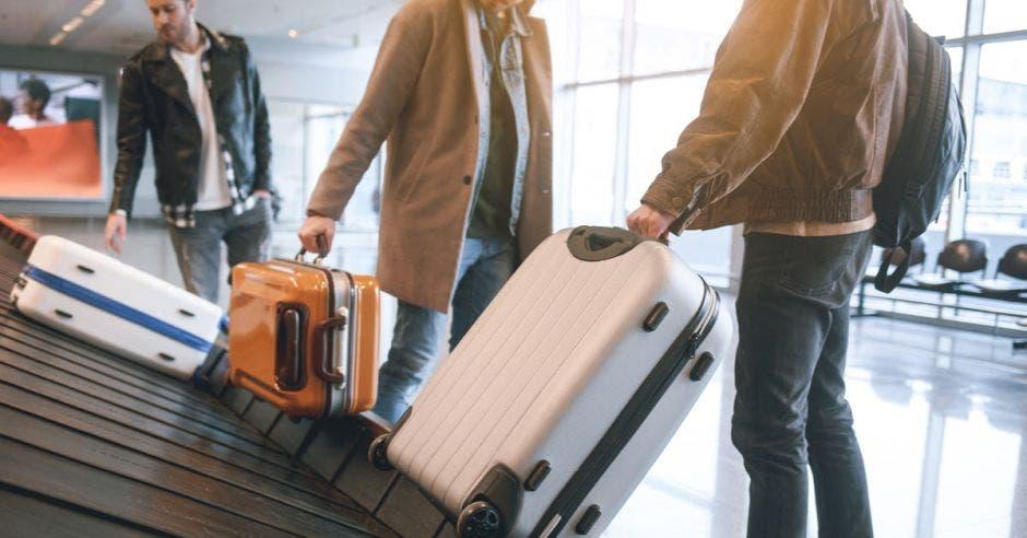 un grupo de personas retira su equipaje de la banda del aeropuerto