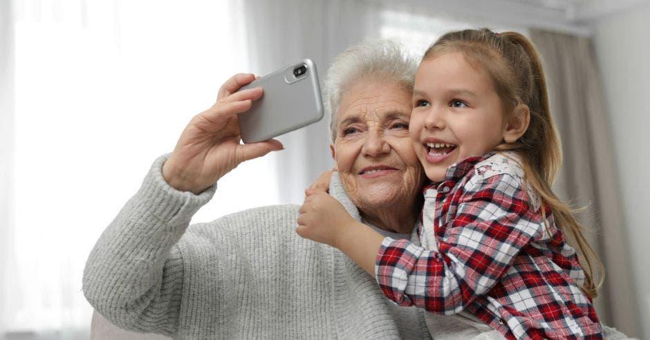Una mujer adulta mayor se toma una selfie con su nieta