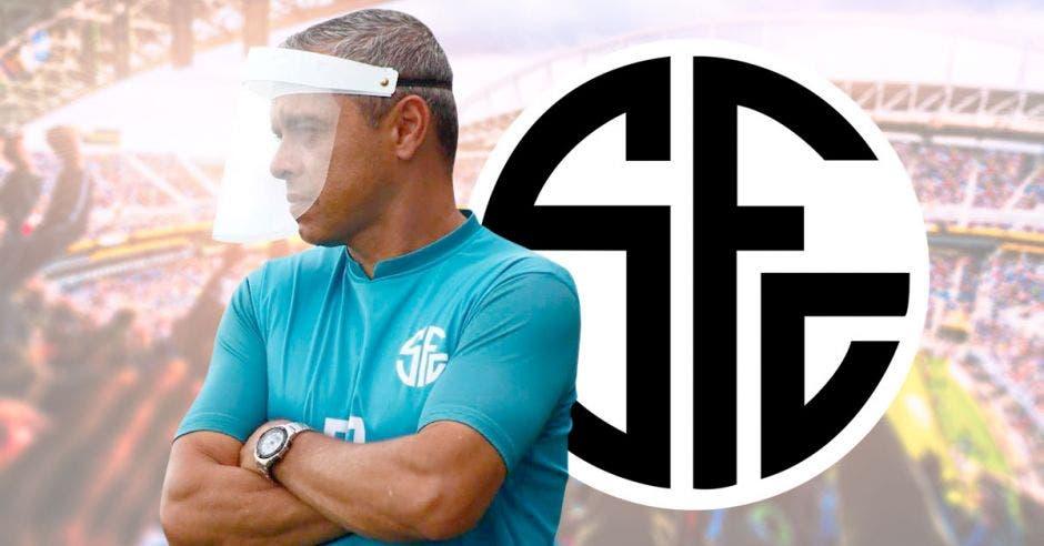 Randall Row, entrenador de fútbol posa frente al escudo de su equipo Sporting FC